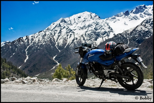 The Pulsar-200 dwarfed by the huge and utterly beautiful snow-clad mountains.